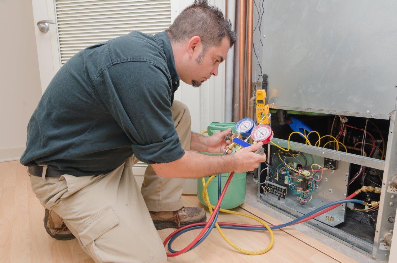 Refrigeristas com manifold analógico nas mãos