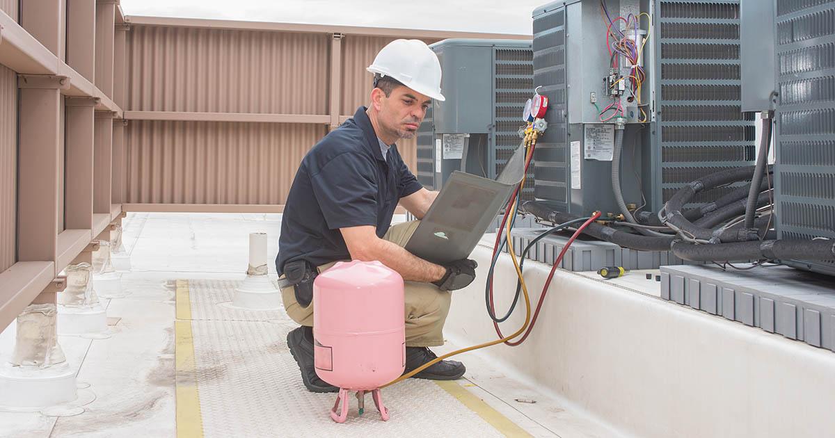 Técnico em refrigeração (refrigerista) fazendo carga de gás