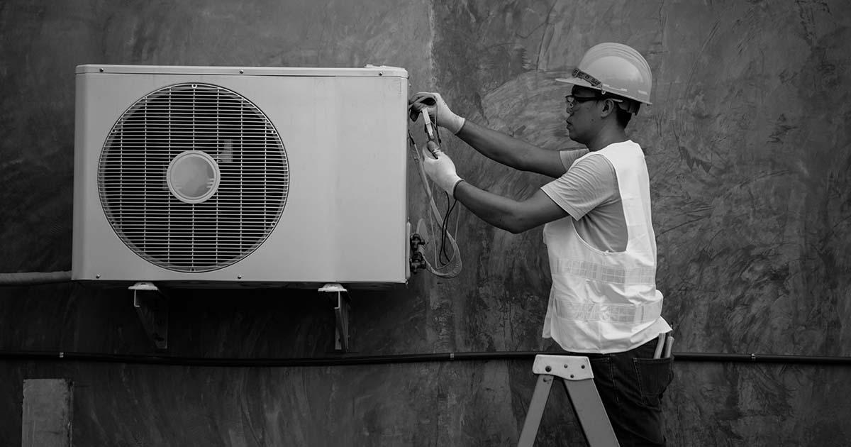 Técnico em ar condicionado fazendo manutenção na condensadora do sistema de climatização