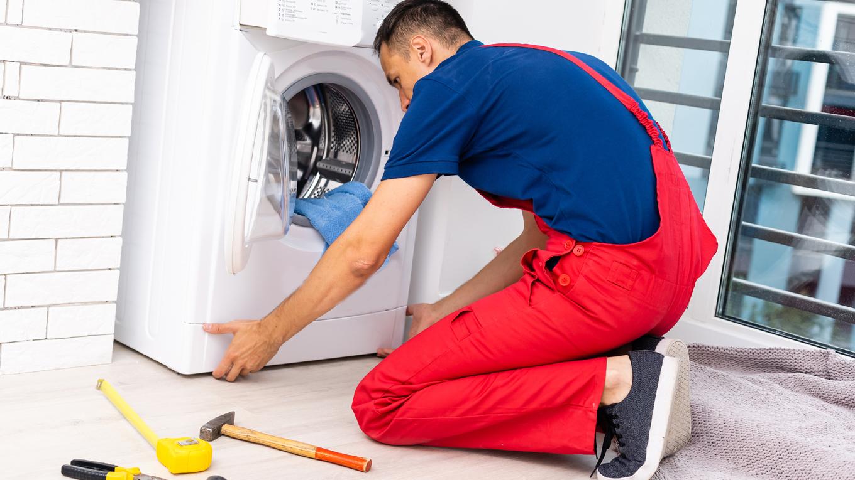 técnico consertando rolamento de máquina de lavar roupas