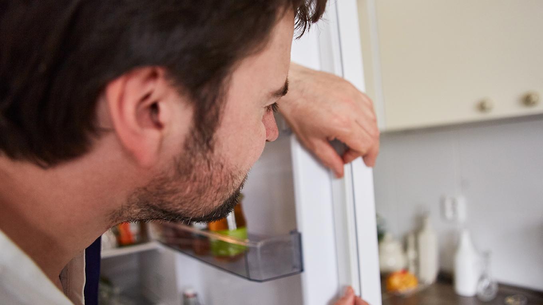 Tecnico realizando a troca da borracha da geladeira