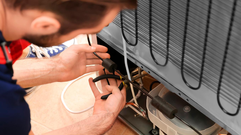 refrigerista fazendo manutencao de pecas de geladeira
